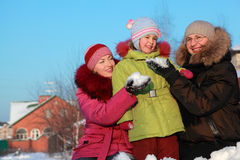 Parents offer to daughter to make snowball Stock Image