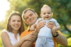 Parents in the park holding his son on arms Royalty Free Stock Photography