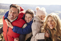 Parents piggy back kids in the countryside, looking away Stock Image