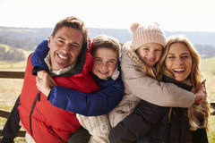 Parents piggy back kids in the countryside looking to camera Royalty Free Stock Photos
