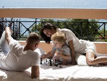 Parents play chess with kid on terrace on sunny day. Family with little son play chess on balcony, nature and sea on. Background. Dad and mom with child play royalty free stock photography