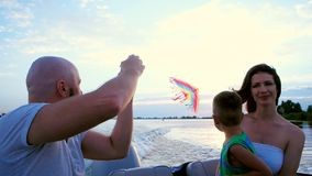 Parents play with a child, family launches kite sitting in a boat, ride on the speed of the boat, a happy child laughing