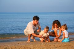 Parents play with children finding shells Stock Photo