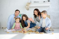 Parents play cubes with children. Joint leisure. Three children of different ages are building something with interest. Everyone has a great mood stock images