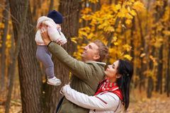 Parents play with little daughter in autumn park royalty free stock photos