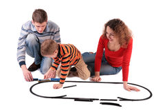 Parents play with son in toy railroad Stock Photo