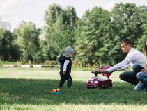 Parents play with their little son on the lawn in the Park. Happy parents play with their little son on the lawn in the Park. photo with copy space stock images