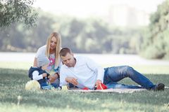 Parents play with their little son sitting on the grass. In the Park stock photos