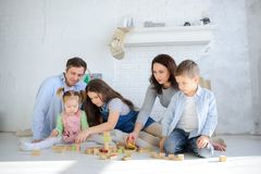 Parents play with their three children. Dad, mother, son and two daughters are sitting on the floor in the room. All together they build something from wooden royalty free stock photos