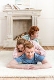 Parents playing with adorable redhead son at home, family fun at home concept. Happy parents playing with adorable redhead son at home, family fun at home Royalty Free Stock Photography