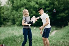 Parents playing with baby daughter in nature. Family leisure. Parents playing with baby daughter in nature. Childhood, parenthood, child development, love Stock Photo