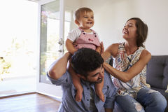 Parents Playing With Baby Daughter On Sofa At Home stock images
