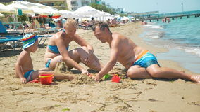 Parents playing with a child on the beach stock video footage