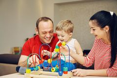 Parents playing with child in developing game. Parents playing with their child in developing game at home. Dad, mom and son having fun Royalty Free Stock Images
