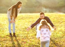 Parents playing with daughter in park at sunset royalty free stock images
