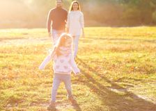 Parents playing with daughter in park at sunset stock photo