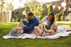 Parents Playing Game With Children On Blanket In Garden stock photos