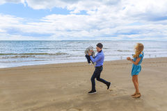 Parents playing with his son on the beach Stock Photography
