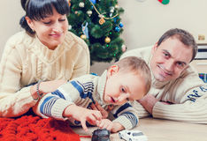 Parents playing with his son with Santa's gifts Royalty Free Stock Image