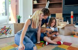 Parents and son playing the tablet. Parents playing the tablet with their son while they rest from the move Stock Photos
