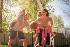 Parents playing with their children in the park with basket ball.  royalty free stock image