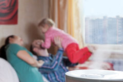 Parents playing with their daughter on the background of humidif. Parents playing with their daughter on the blured background of humidifier Stock Photo