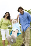 parents playing with their daughter in the park Stock Image