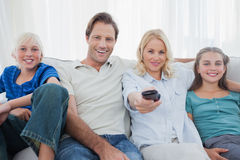 Parents posing with children and watching television Royalty Free Stock Image