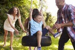 Parents poussant des enfants sur l'oscillation de pneu dans le jardin Images libres de droits
