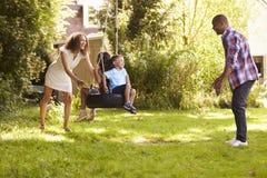 Parents poussant des enfants sur l'oscillation de pneu dans le jardin Images stock