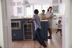 Parents Prepare Food As Children Play In Kitchen Stock Photography