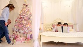 Parents prepared New Year`s gifts for their two sons, while boys play games on gadget in newly decorated bedroom with stock video