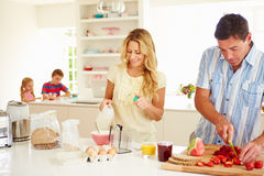 Parents Preparing Family Breakfast In Kitchen. With Children Sitting In Background Stock Photo