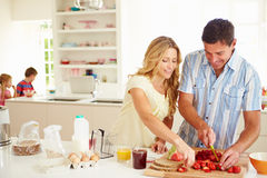 Parents Preparing Family Breakfast In Kitchen. Cutting Strawberries Smiling Stock Images