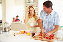 Parents Preparing Family Breakfast In Kitchen. Looking At Each Other Smiling With Children In Background Stock Images