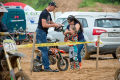 Parents are preparing to start. MOSCOW, RUSSIA - JULY 1, 2017: Parents-trainers prepare a young rider for the start in the Velyaminovo Race Weekend 2017 Stock Photos