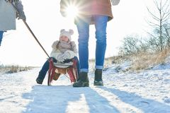 Parents pull child with sled in the snow Stock Photography