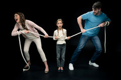 Parents pulling over shocked daughter with rope,. Divorce and separation concept Stock Photos