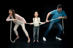 Parents pulling over shocked daughter with rope,. Divorce and separation concept Stock Image