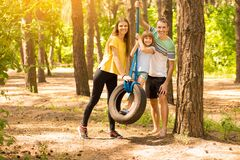 Parents pushing child daughter on tire swing in park