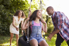 Parents Pushing Children On Tire Swing In Garden Royalty Free Stock Photos