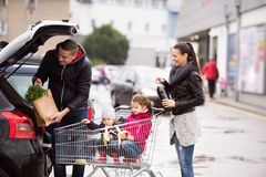 Parents pushing shopping cart with groceries and their daughters Royalty Free Stock Image