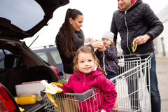 Parents pushing shopping cart with groceries and their daughters Royalty Free Stock Photos