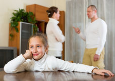 Parents quarrel at home. Parents and daughter quarrel at home. Focus on girl royalty free stock photo