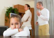 Parents quarrel at home. Sad daughter and parents having quarrel at home. Focus on girl stock photography