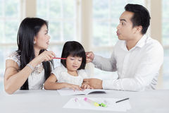 Parents quarreling while their daughter crying. Picture of two young parents quarreling at home while their daughter listening and crying Stock Image