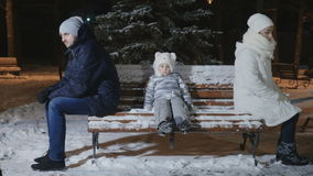 Parents quarrelled and sit backs on the bench, little sad girl between them stock footage