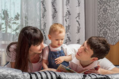 Parents read book child. Young family for reading books Royalty Free Stock Photo