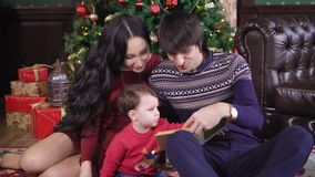 Parents read to their son a Christmas fairy tale sitting on a carpet near a fir-tree decorated with New Year`s Eve stock video