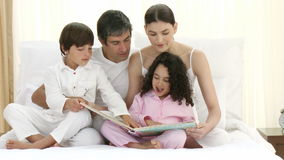 Parents reading a book on bed with their children Stock Photography